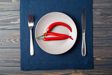 Gray plate with chilli red pepper on , spoon and knife with blue linen tablecloth on table top view Reklamní fotografie