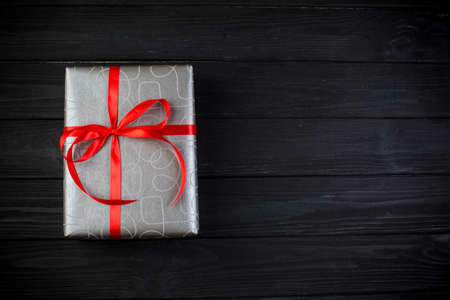 Grey silver gift box with red ribbon bow on black wooden table. Boxing day Reklamní fotografie