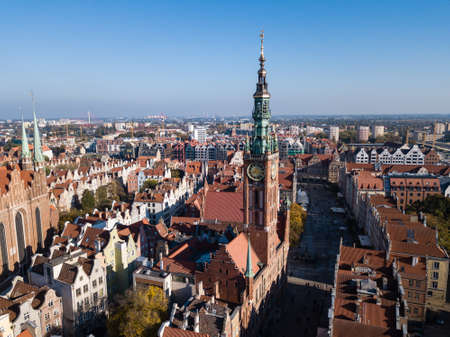 Aerial view of old historical town centre with typical colorful houses buildings, tiled roofs and City Hall spire clock tower, Gdansk, Poland