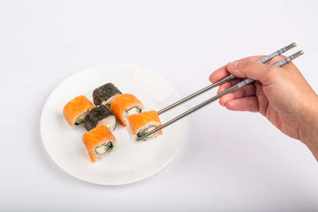 Roll of sushi on a plate, Sushi roll on a tablet, white background, Sushi roll and hand with chopsticks. Japanese food 免版税图像