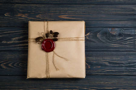Vintage Christmas gift wrapped in craft paper, tied with string and glued wax seal. Lying on the black wooden table
