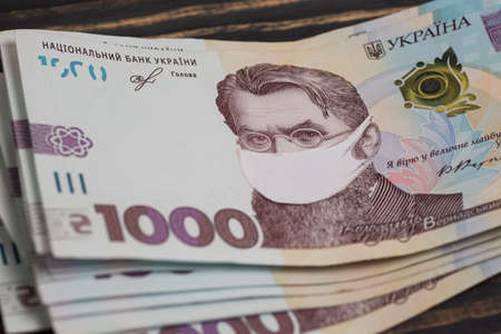 Coronovirus crisis concept - money of Ukraine with protective mask on it. Stack of ukrainian hryvnia banknotes in gloved hands on wooden table. Hryvnia 1000 uah