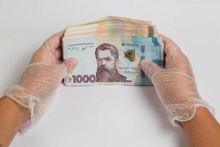 Money of Ukraine. Stack of ukrainian hryvnia banknotes in gloved hands on white. Hryvnia 1000 uah Banque d'images