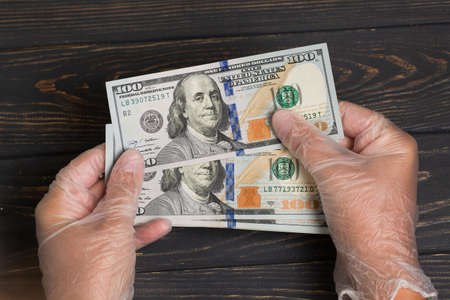 Stack of 100 dollars USA in gloved hands on wooden table Standard-Bild