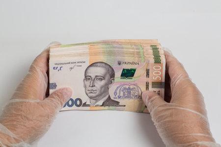 Money of Ukraine. Stack of ukrainian hryvnia banknotes in gloved hands on white. Hryvnia 500 uah