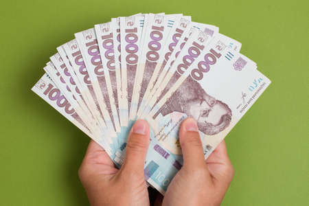 Stack of new ukrainian hryvnia banknotes in hands on green background. Hryvnia 1000 uah
