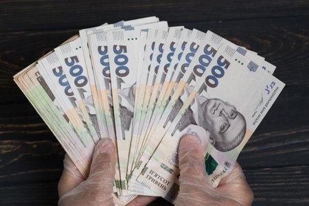 Money of Ukraine. Stack of ukrainian hryvnia banknotes in gloved hands on wooden table. Hryvnia 500 uah Banque d'images