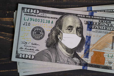 Coronovirus crisis concept - money of USA with protective mask on it. Stack of dollars banknotes on wooden table. USA 100 usd
