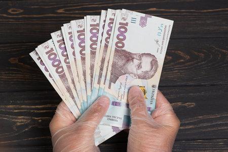 Money of Ukraine. Stack of ukrainian hryvnia banknotes in gloved hands on wooden table. Hryvnia 1000 uah Banque d'images