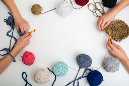 Different colored balls of yarn. Children's hands are crocheted and thread view frome above with place for text Standard-Bild