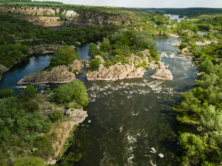 Aerial view to granite mountains and rapids on Southern Bug river, surrounded by trees and grasses, Mihiia village. Ukraine. Famous place for rafting and kayaking