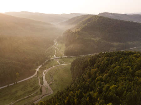 Spectacular aerial view to road with moutains captured from above at sunrise, carpathians mountains