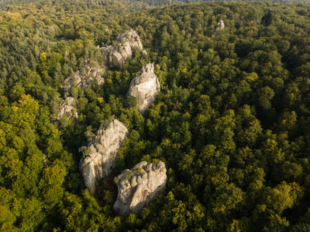 Aerial view to Dovbush Rocks in Bubnyshche at sunrise. Legendary ancient cave monastery in fantastic boulders amidst beautiful scenic forests in Carpathian Mountains, Ukraine