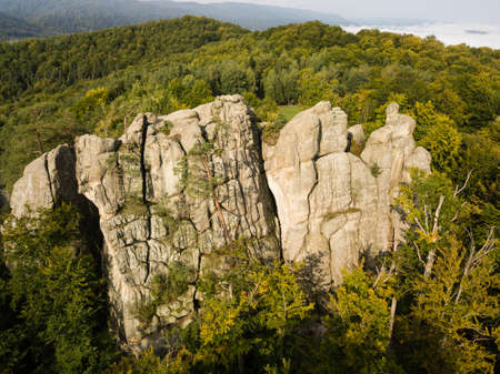 Aerial view to Dovbush Rocks in Bubnyshche at sunrise. Legendary ancient cave monastery in fantastic boulders amidst beautiful scenic forests in Carpathian Mountains, Ukraine Standard-Bild