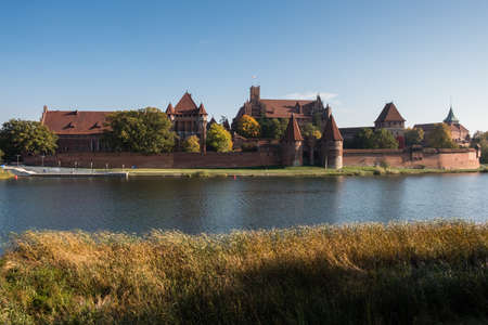 View to the Malbork Castle in Poland and its reflection in river Nogat at summer sunny day Editorial