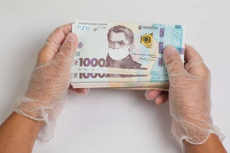 Coronovirus crisis concept - money of Ukraine with protective mask on it. Stack of ukrainian hryvnia banknotes in gloved hands on white. Hryvnia 1000 uah