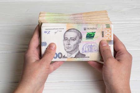Money of Ukraine. Stack of ukrainian hryvnia banknotes in hands on wooden table. Hryvnia 500