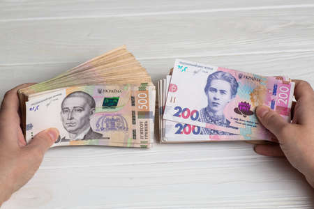 Money of Ukraine. Stack of ukrainian hryvnia banknotes in hands on wooden table. Hryvnia 500 and 200 uah Stock fotó