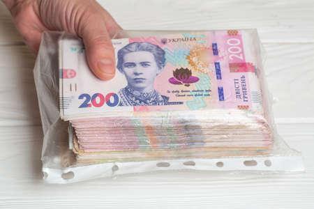Money of Ukraine. Stack of ukrainian hryvnia banknotes in plastic transparent bag in hands