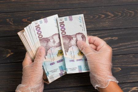 Money of Ukraine. Stack of ukrainian hryvnia banknotes in gloved hands on wooden table. Hryvnia 1000 uah Stock fotó
