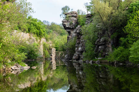 Calm river flowing in canyon with overhanging cliffs on two banks, Buky Canyon, near village Buki, Cherkassy region, Ukraine