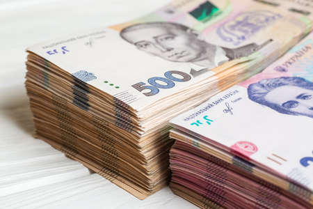 Money of Ukraine. Stack of ukrainian hryvnia banknotes in hands on white wooden table. Hryvnia 200 and 500 Stock fotó