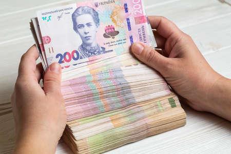 Money of Ukraine. Stack of ukrainian hryvnia banknotes in hands on wooden table. Hryvnia 200 uah Stock fotó