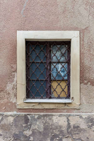 gratings: Old, decayed windows on a broken wall.