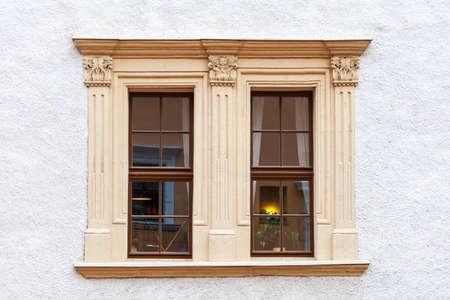 gratings: A brown, wooden window.