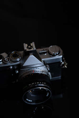 retro photo camera with leather strap on a black background