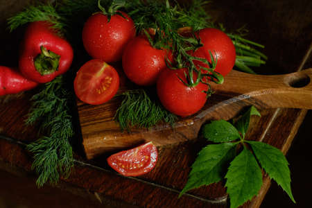 Red vegetables and greens on a rustic board. In the frame you can see a slice of tomato and a leaf of wild grapes and dill