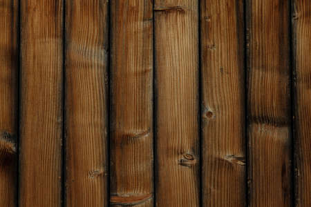 Vertical old shabby wooden boards. Brown scuffed boards