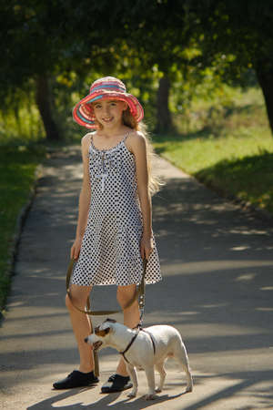 Girl and Jack Russell Terrier walk in the park Archivio Fotografico - 130718819