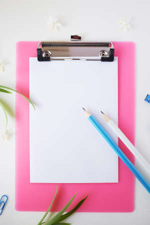 Pencils, a sheet of paper and plants are visible in the frame. Clipboard mockups.