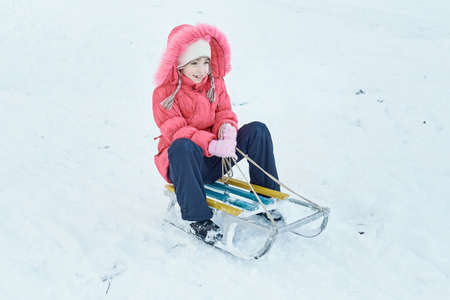A girl sits on a sled in a park in the snow. Girl wearing a hat and a pink coat