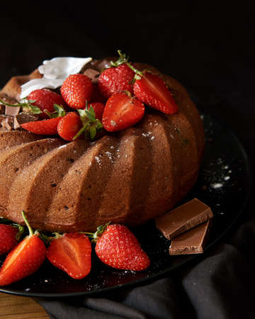 Chocolate cake light brown with red strawberries. Black background