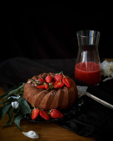Chocolate cake light brown with red strawberries. Cake sprinkled with powdered sugar. Black background
