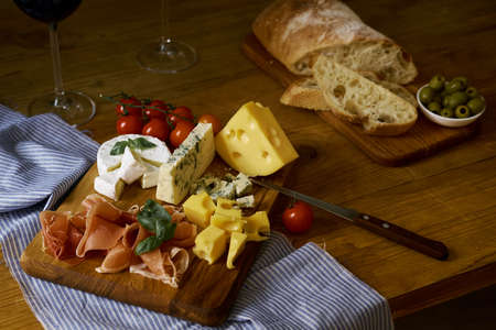 Various snacks on wooden boards on tablecloths lie on the table