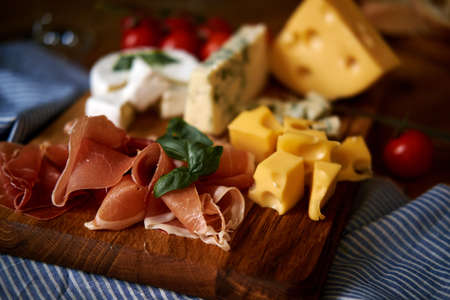 Several types of cheese, meat on a board on a tablecloth. closeup