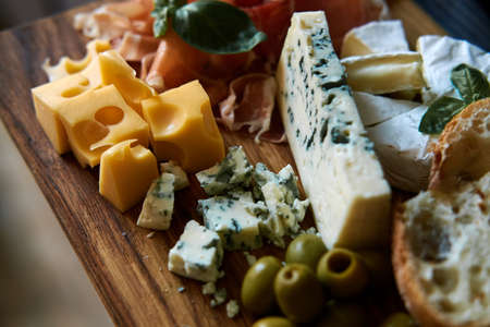 Several types of cheese and other snacks lie on a wooden board.
