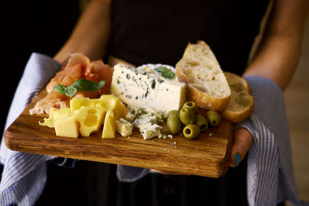 Female hands hold a wooden board with various snacks. A tablecloth is visible in the frame