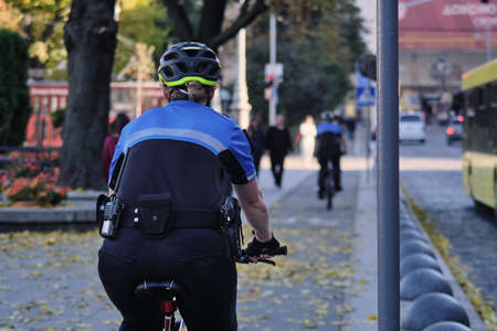 A female police officer on a bicycle patrols the streets in Ukraine. A female policeman in a blue uniform on a bicycle patrols the streets in Ukraine. Frame taken from the back
