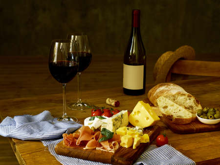 On a wooden table is a bottle of wine, two glasses of wine and snacks. black background