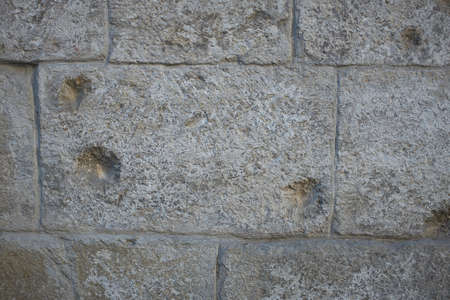 Gray antique stone wall of a house with bullet marks
