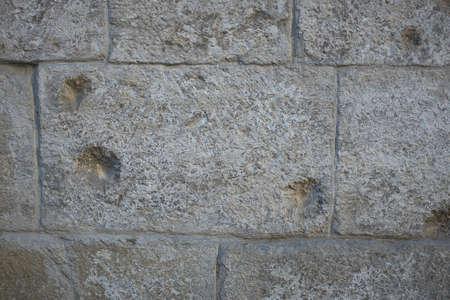 Szara antyczna kamienna ściana domu ze śladami po kulach