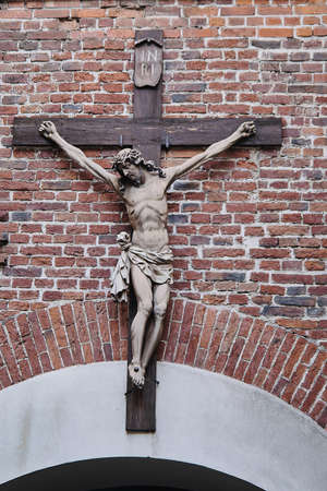 Small statue of the crucified Jesus Christ on the brick facade of the Armenian church Banco de Imagens