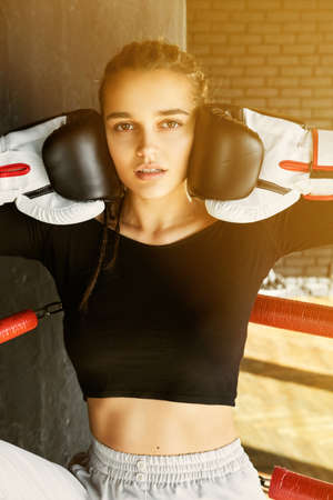 A young girl in boxing gloves and a black T-shirt stands in the ring. The girl is filmed waist-high closeup. Gloves pressed to face Stock Photo