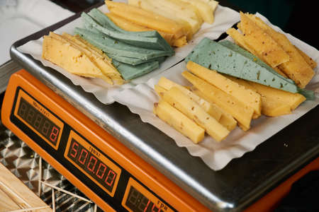 Slices of different varieties of cheese are weighed on a scale. Фото со стока