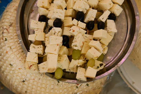 Cheese cubes and olives are strung on sticks, below is a large head of cheese
