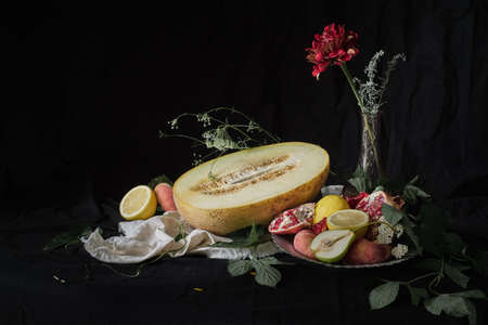 Melon sliced surrounded by fruits on a black background